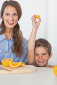 Little boy raising an orange segment — Stock Photo