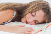 Cute girl sleeping while holding a book — Stock Photo