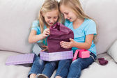 Young twins unwrapping birthday gift sitting on a couch — Stock Photo