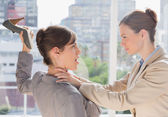 Businesswoman defending herself from her co worker strangling he — Stockfoto