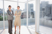 Smiling businesswomen standing in bright office — Stock Photo