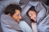 Couple having fun wrapped in their blanket — Stock Photo