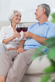 Wife and husband clinking their glasses of red wine — Stock Photo