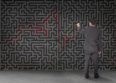 Rear view of a businessman drawing a red line through black maze — Stock Photo