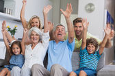 Multi-generation family raising their arms — Stock Photo