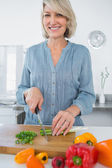 Smiling woman chopping vegetables — Stock Photo