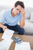 Fearful man doing his accounts with a calculator — Stock Photo