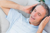 Man lying on sofa listening to music with eyes closed — Stock Photo