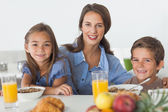 Mother having breakfast with her children — Stock Photo