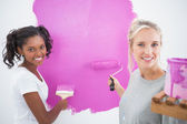 Smiling housemates painting wall pink — Stock Photo