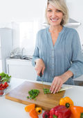 Cheerful woman chopping vegetables — Stock Photo