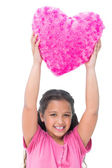 Smiling little girl holding cushion in the shape of a heart — Stock Photo