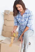 Woman wrapping a box — Stock Photo