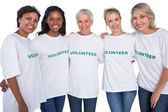 Group of female volunteers smiling at camera — Stock Photo