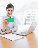 Pretty businesswoman showing green business card — Stock Photo