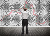 Confused businessman looking at a maze — Stock Photo