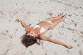 Sunbathing woman lying on beach — Stock Photo
