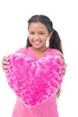 Little girl showing cushion in the shape of a heart — Stock Photo