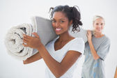 Happy housemates carrying rolled up rug — Stock Photo