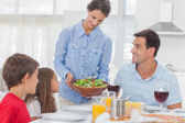 Pretty woman bringing a salad to her family — Stock Photo
