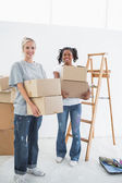 Pretty young housemates carrying moving boxes — Stock Photo