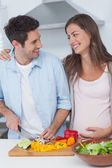 Pregnant woman looking at husband chopping vegetables — Stock Photo