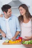 Pregnant woman looking at husband chopping vegetables — Stock Photo