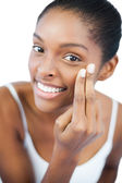 Smiling woman putting moisturizer on her face — Stock Photo