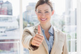 Happy businesswoman giving thumb up to camera — Stock Photo