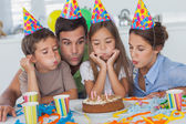 Family blowing candles together — Stock Photo