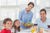 Portrait of a woman bringing a salad to her family — Stock Photo