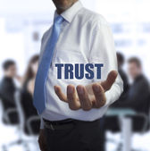 Sophisticated businessman holding the word trust — Stock Photo