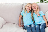Blonde twins sitting on a couch — Stock Photo