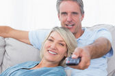 Cheerful couple relaxing at home watching tv — Stock Photo