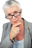 Thinking mature woman wearing glasses — Stock Photo