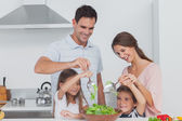 Family mixing a salad together — Stock Photo