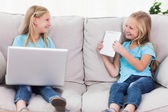 Young twins using a laptop and a tablet sitting on a couch — Stock Photo