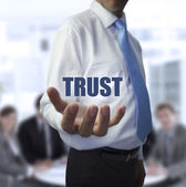 Elegant businessman holding the word trust — Stock Photo
