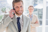 Businessman having phone conversation and smiling at camera — Stock Photo