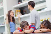 Couple arguing behind their children — Stock Photo