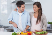 Man chopping vegetables next to his pregnant partner — Stock Photo
