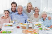 Extended family smiling at dinner family — Stock Photo