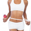 Woman holding apple and measuring her waist — Stock Photo #28060017