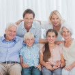 Extended family sitting together on couch — Stock Photo