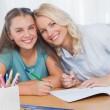 moeder helpen dochter met huiswerk in woonkamer — Stockfoto