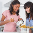 Cheerful friends preparing spaghetti dinner together — Stock Photo