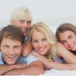 Smiling family lying on bed — Stock Photo