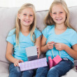 Stock Photo: Cute twins unwrapping birthday gift sitting on couch