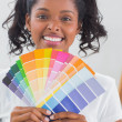 Smiling woman showing colour charts — Stock Photo #28060339