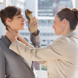 Businesswoman strangling another who is defending with her shoe — Stock Photo #28060427
